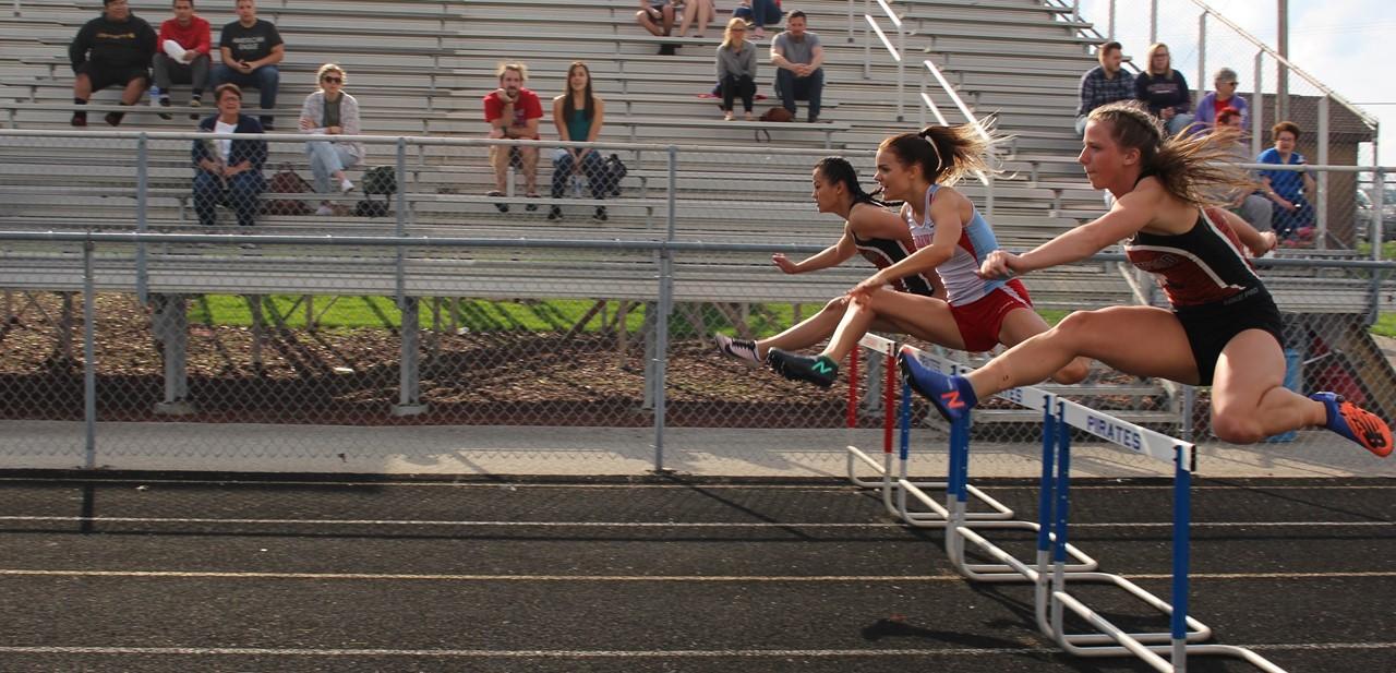 Students jumping hurdles.
